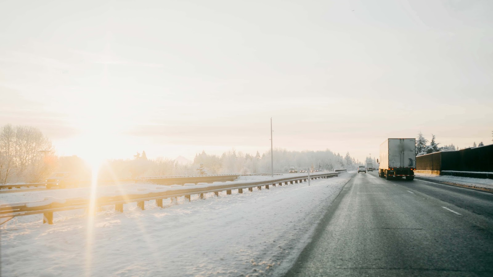 semi-truck driving on highway during winter