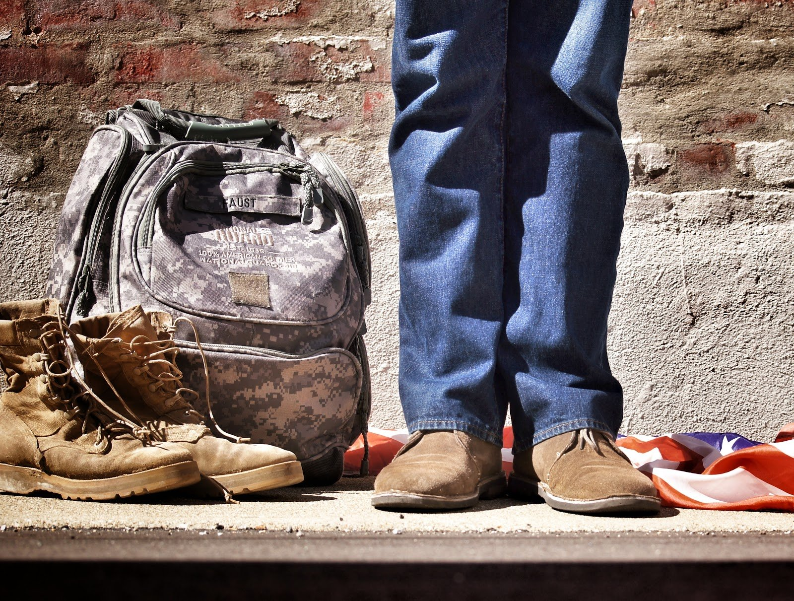 veteran standing next to boots and backpack
